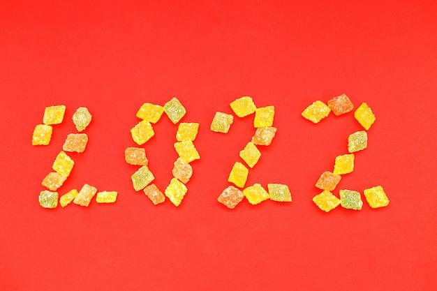 Numeral 2022 de doces multicoloridos em fundo vermelho