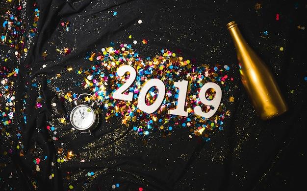 Numeral decorativo brilhante 2019 com garrafa dourada