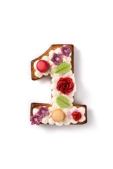 Numere um bolo decorado com flores e macarons em branco.