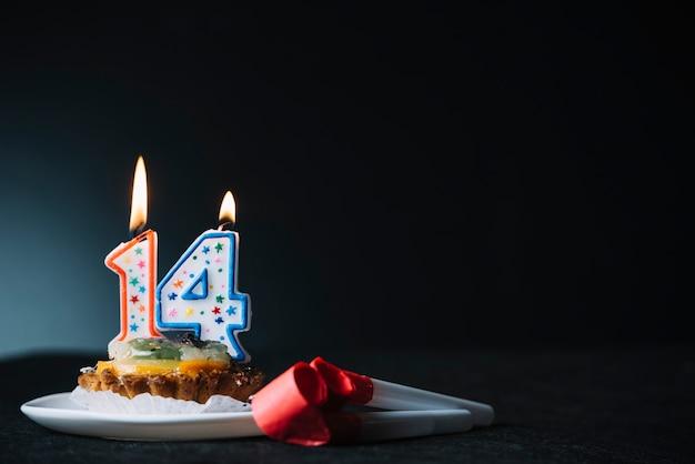 Número 14 aniversário iluminado vela sobre a fatia de soprador de chifre de torta e festa contra o pano de fundo preto