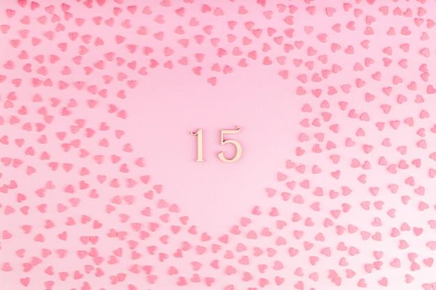Número 15 quinze de madeira em decoração em forma de coração com pequenas corações