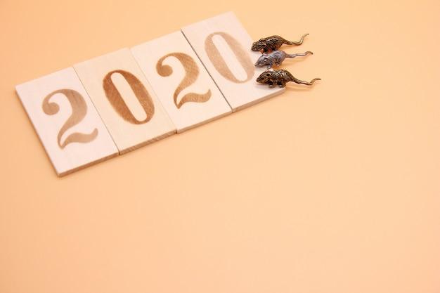 Número 2020 alinhado com figuras de madeira e três ratinhos de metal nele.