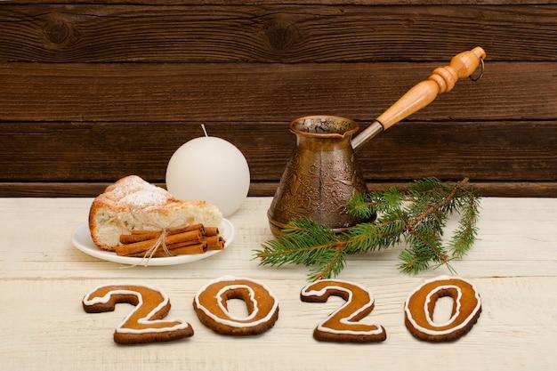 Número 2020 de biscoitos de gengibre. cezve, torta, ramos de abeto e vela. natal