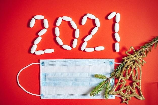 Número 2021, feito de comprimidos e uma máscara médica protetora sobre um fundo vermelho.