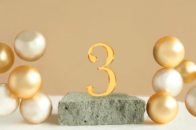 Número 3 em um pódio de concreto e bolas douradas volumétricas em um fundo bege. copie o espaço.