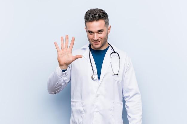 Número alegre cinco de sorriso mostrando cinco do homem considerável novo do doutor com dedos.