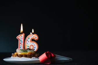 Número de aniversário de 16 anos acendeu a vela na fatia de soprador de chifre tart e festa contra o fundo preto