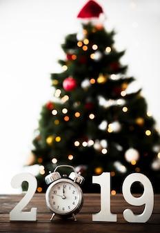 Número de ano novo na tabela com relógio e abeto