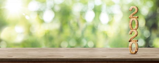 Número de madeira do ano novo 2020 na mesa de madeira no borrão bandeira verde abstrata