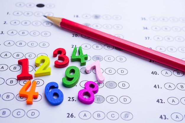 Número de matemática colorido e lápis na folha de respostas: educação estudar matemática aprendizagem.