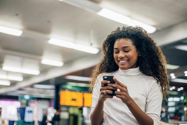 Número de voo de seleção de mulher no telemóvel no aeroporto.