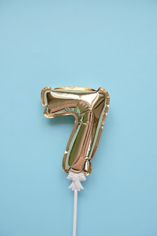 Número inflável de ouro 7 em uma vara sobre um fundo azul. conceito de feriado, aniversário, aniversário.