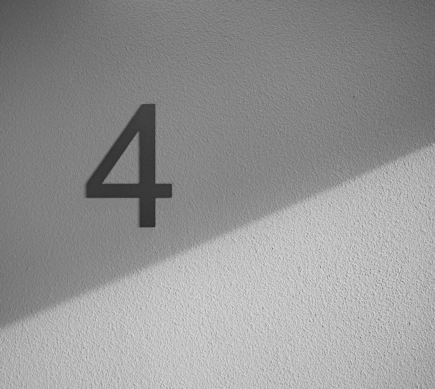 Número quatro na parede branca close-up
