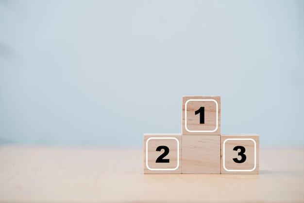 Número um, dois e tela impressa em árvore em um bloco de madeira para o segundo e segundo colocado vencedor na cerimônia do pódio.