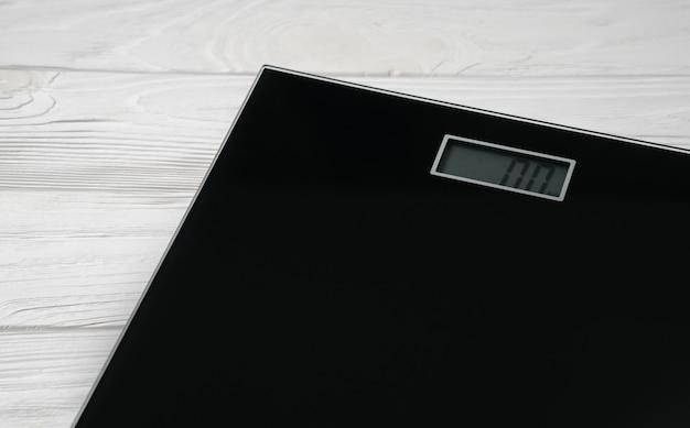 Número zero na tela da balança de banheiro digital na parede de madeira branca