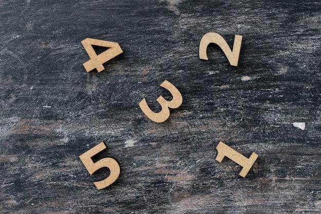 Números 1, 2, 3, 4, 5 em uma mesa de madeira vintage escura.