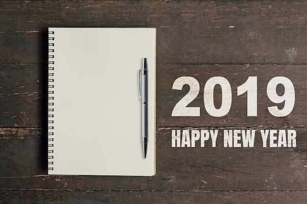 Números 2019 feliz ano novo e notebook com caneta para espaço de cópia.