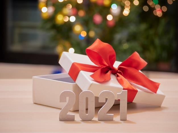 Números 2021 contra árvore de natal desfocada, luz bokeh