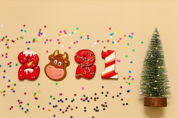Números 2021 de biscoitos de gengibre em esmalte multicolorido sobre fundo bege. o símbolo do touro do ano, estrelas multicoloridas e uma árvore de natal. ano novo 2021, feriado de natal