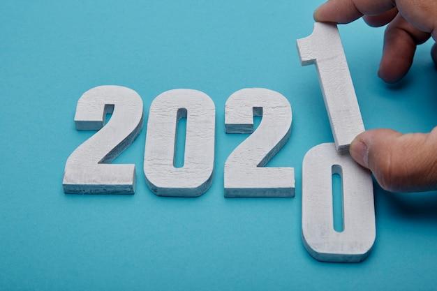 Números 2021 e mão sobre fundo azul pastel para o ano novo