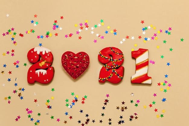 Números 2021 feitos de biscoitos de gengibre em esmalte multicolorido sobre fundo bege. coração vermelho e estrelas multicoloridas. ano novo 2021, feriado de natal