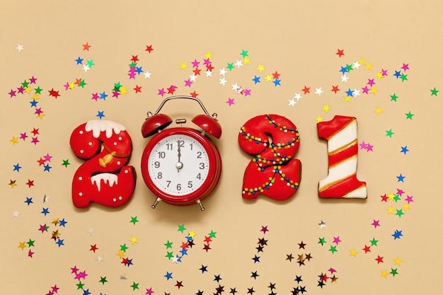 Números 2021 feitos de biscoitos de gengibre em esmalte multicolorido sobre fundo bege. despertador vermelho e estrelas multicoloridas. ano novo 2021, feriado de natal