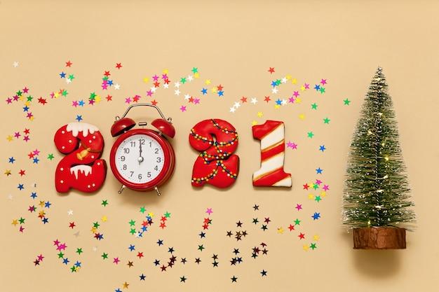 Números 2021 feitos de biscoitos de gengibre em esmalte multicolorido sobre fundo bege. despertador vermelho, estrelas multicoloridas e uma árvore de natal. ano novo 2021, feriado de natal