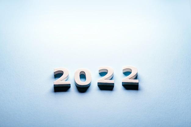 Números brancos 2022 em um fundo azul cartão postal do minimalismo 2022corte os números 2022merry