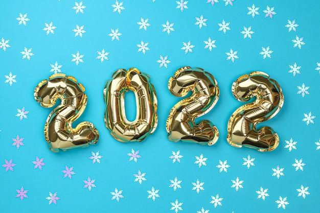 Números de balões de folha de ano novo em fundo azul ano novo natal