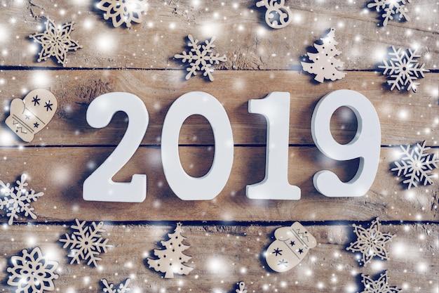Números de madeira, formando o número 2019, para o ano novo e a neve branca com flocos de neve em