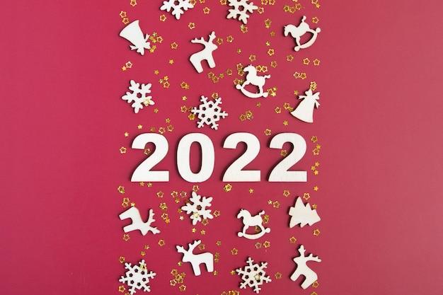 Números de madeira para o ano novo de 2022 com estrelas e decoração de natal em fundo vermelho