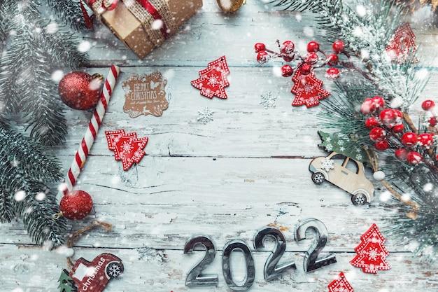 Números de prata 2022 em um fundo de madeira com decorações de natal e espaço de cópia de flocos de neve