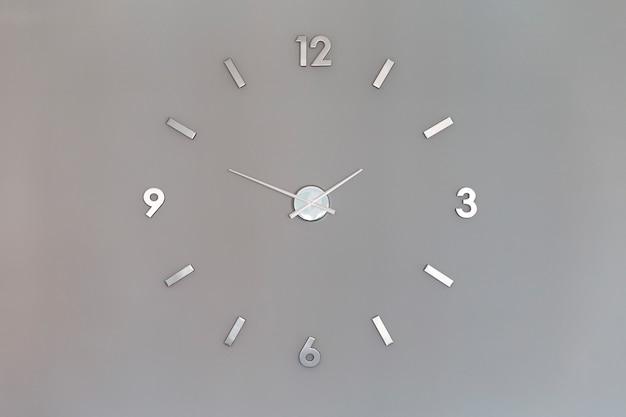 Números de prata relógio brilhante na parede com espaço de cópia