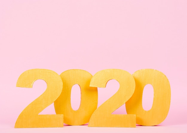 Números do ano novo 2020 em fundo rosa com espaço de cópia