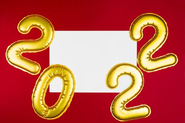 Números dourados de ano novo com lista de papel branco em vermelho com espaço de cópia