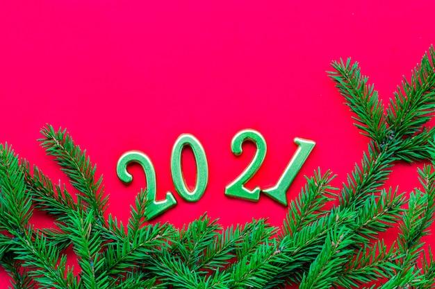 Números dourados e fundo vermelho sólido de galho de árvore de natal verde. ano novo e natal