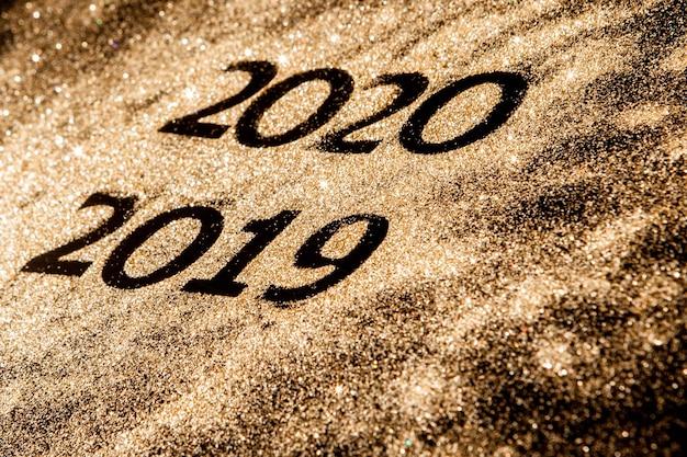 Números dourados espumantes bonitos de 2019 a 2020 em fundo preto