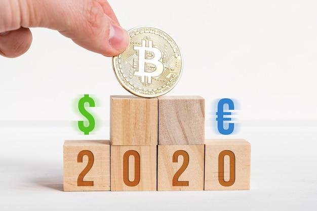 Números em cubos de madeira em um fundo branco ao lado de uma moeda de bitcoin e sinais de dólar e euro.