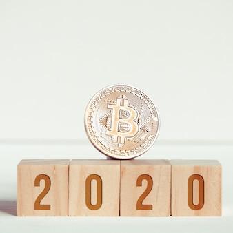 Números em cubos de madeira em um fundo branco ao lado de uma moeda de bitcoin.