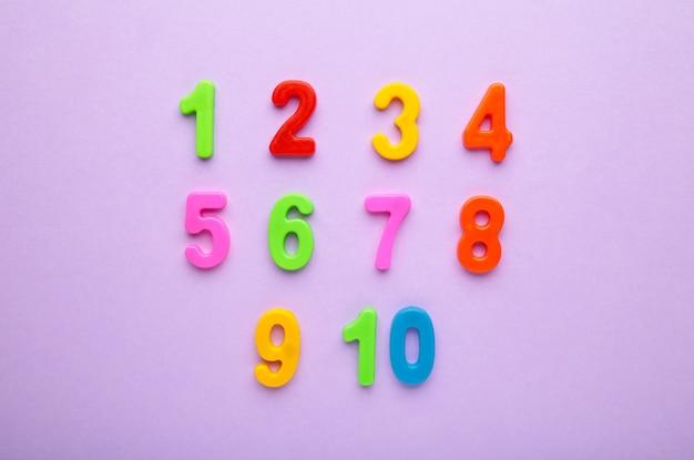 Números magnéticos multicoloridos sobre fundo roxo com espaço de cópia. de volta à escola.