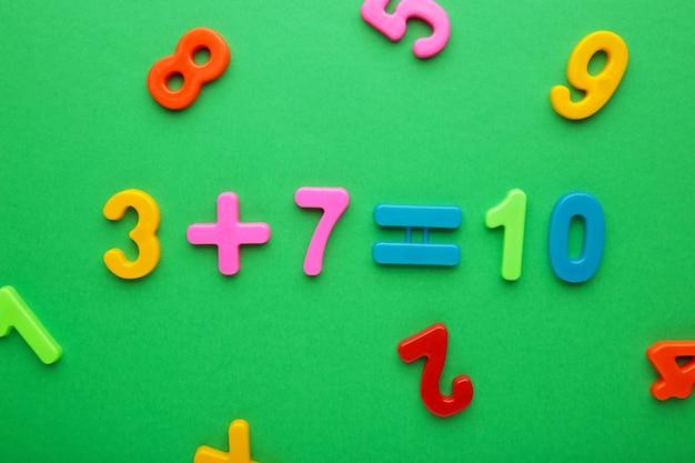 Números magnéticos multicoloridos sobre fundo verde com espaço de cópia. de volta à escola.