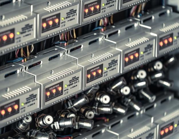 Numerosos plugues redondos de metal conectados uns aos outros por fios pendurados entre painéis iluminados por sensores eletrônicos na fabricação de peças de navios. conceito de indústria