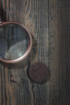 Numismática. moedas antigas de colecionador e uma lupa sobre uma mesa de madeira. fundo escuro. vista do topo.