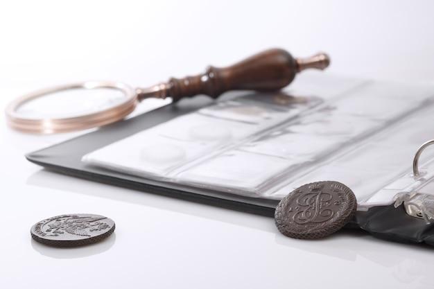 Numismática. moedas colecionáveis antigas e uma lupa em cima da mesa. fundo claro.