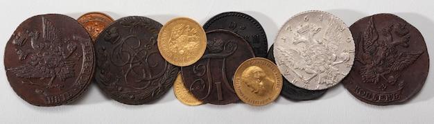 Numismática. moedas colecionáveis antigas feitas de prata, ouro e cobre em uma mesa de madeira. vista do topo.