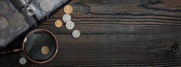 Numismática. moedas colecionáveis velhas em uma mesa de madeira. fundo escuro. bandeira. copie o espaço do seu texto.