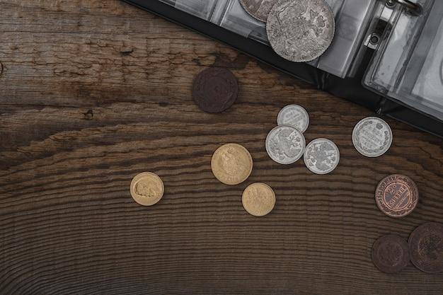 Numismática. moedas colecionáveis velhas em uma mesa de madeira. fundo escuro. vista do topo.