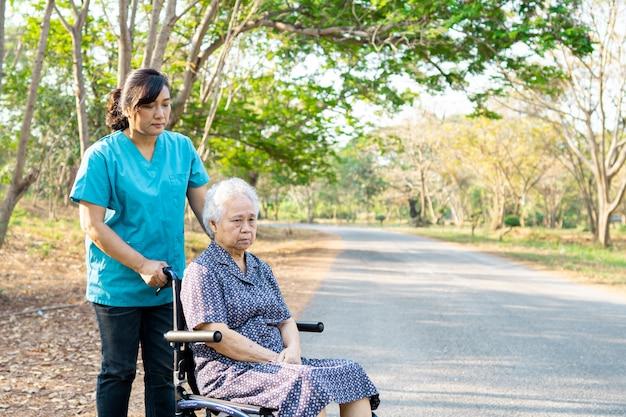 Nutra a ajuda e importa-se o paciente sênior asiático da mulher que senta-se na cadeira de rodas no parque.