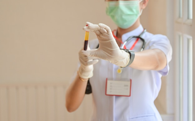 Nutra luvas usando um tubo de análise de sangue dianteiro, conceitos que examinam a infecção pelo vírus covid-19.