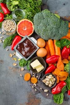 Nutrição de dieta equilibrada, conceito de alimentação limpa e saudável. variedade de fontes de alimentos ricos em vitamina a na mesa da cozinha. plano de fundo vista de cima